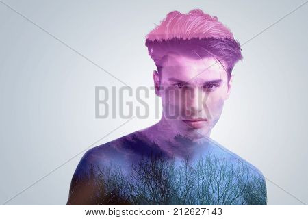 Majestic nature. Dark mystique nature  charming innocent naive focused guy who gazing straight and posing on the grey background
