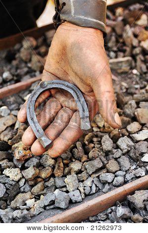 Detail of dirty hand holding horseshoe - blacksmith poster
