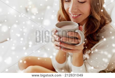winter, cosiness, leisure and people concept - close up of happy young woman with cup of coffee or cacao at home over snow