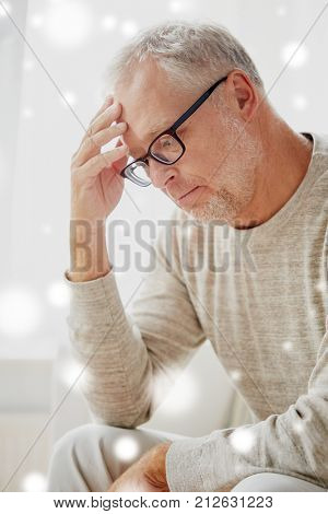 stress, old age and people concept - senior man suffering from headache over snow