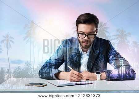 Concentration. Smart scrupulous experienced worker sitting at the table and looking concentrated while writing a report