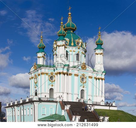 Green baroque St. Andrew's Church or the Cathedral of St. Andrew located in city centre, main sightseeing Andriyivskyy Descent in Kiev, Ukraine. Panoramic view against blue autumn sky. poster