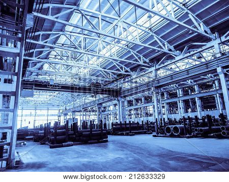 Unified standard typical span prefabricated of a reinforced concrete frame production building. Industrial metalwork production hall. Background in blue tone.