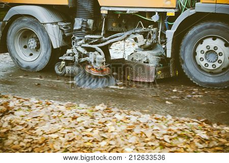 BADEN, GERMANY - NOV 21, 2014: Wheels detail of in motion orange street sweeper truck on the street working cleaning autumn foliage