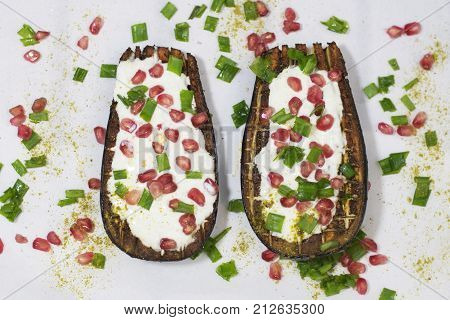 Baked eggplants with garlic yoghurt sauce and pomegranate. White background. Top view