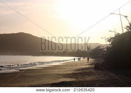 CANASVIEIRAS, SANTA CATARINA, BRAZIL - MARCH 21, 2009: A sunrise on the beach of Canasvieiras. Quiet morning on the beach with some people walking and enjoying.