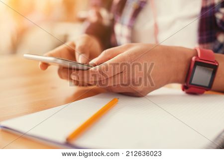 Convenient device. Good equipped fashionable smartphone in the hands of a modern stylish student with a smart watch on her wrist