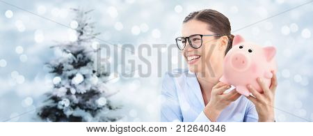 christmas shopping laughing fun woman with piggy bank isolated on blurred lights with tree