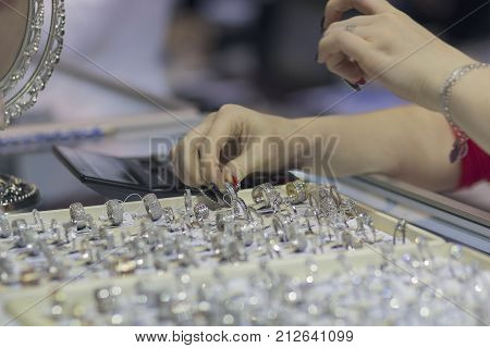 Girl - seller shows the jewelry at the counter. Sales