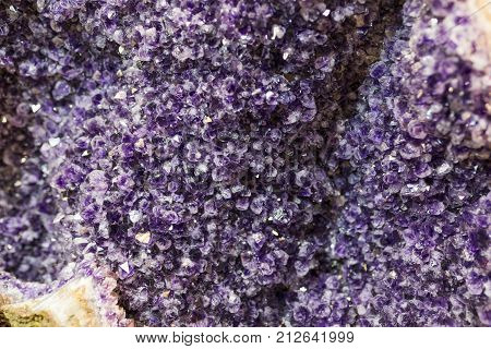 Precious amethyst gemstone and violet crystals in geode