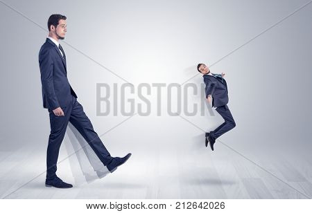 Big man in suit kicking out little himself with simple white wallpaper