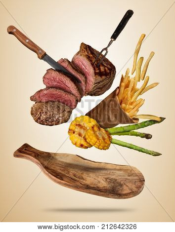 Flying beef steaks with grilled vegetable and french fries served on wooden cutting board. Concept of flying food. Separated on soft colored background. High resolution size
