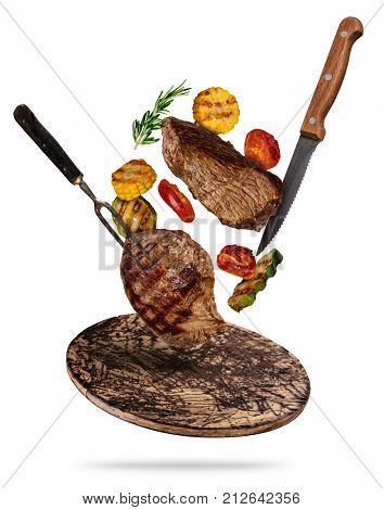 Flying beef steaks with grilled vegetable served on wooden cutting board. Concept of flying food. Separated on white background. High resolution size