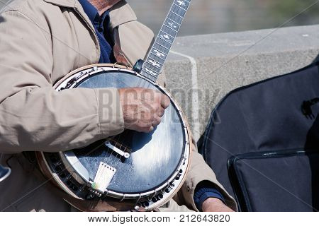 Old man man playing the banjo on the bridge