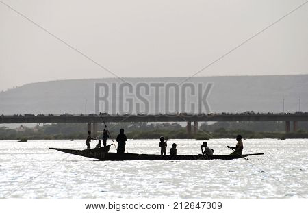 BAMAKO, MALI - CIRCA FEBRUARY 2012: Silhouette of Bozo fishermen and children on a pirogue on the river Niger in Bamako.
