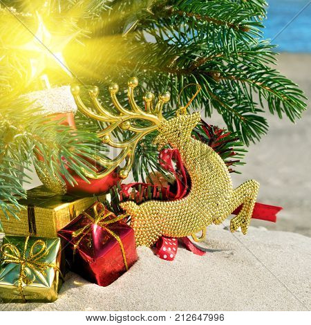 Christmas toys reindear and christmas tree on sea background.