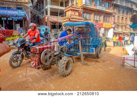 BHAKTAPUR, NEPAL - NOVEMBER 04, 2017: Unidentified people walking close to a small truck at Taumadhi Square in Bhaktapur, Valley, Nepal.
