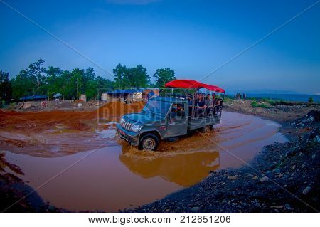 CHITWAN, NEPAL - NOVEMBER 03, 2017: Unidentified people traveling in the back part of a car, crossing a street with dirty water, happy tourists for jungle safari at Chitwan National Park, Nepal, fish eye effect.