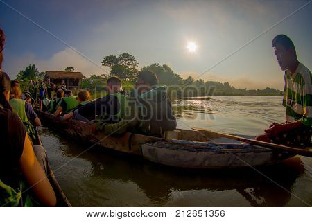 CHITWAN, NEPAL - NOVEMBER 03, 2017: Unidentified people canoeing safari on wooden boats Pirogues on the Rapti river, in a beautiful sunny day in Chitwan National Park, Nepal, fish eye effect.