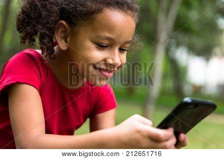 Hispanic kid using her mobile phone