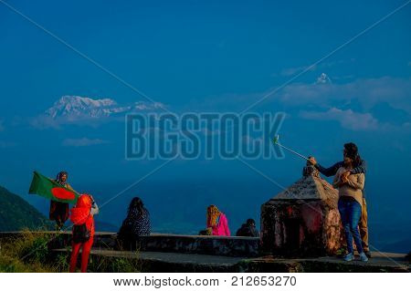 POKHARA, NEPAL, SEPTEMBER 04, 2017: Unidentified tourists at hilltop of the Sarangkot lookout point, holding flags and taking selfies in the mountain to view Annapurna Range during sunrise at Sarangkot, Nepal.
