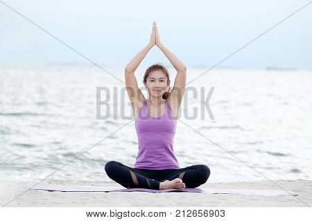 Young healthy asian woman practicing yoga in namaste posture on the beach healthy lifestyles wellness well being