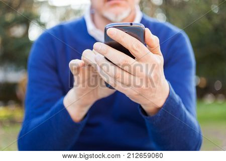 Senior man using his cell phone in a park