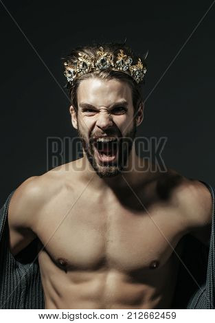Man or cinderella prince in crown shout on grey background. Fashion jewelry accessory. Freak gay and transvestite with naked torso. Drag queen homosexual and trans. Glory nobility triumph.