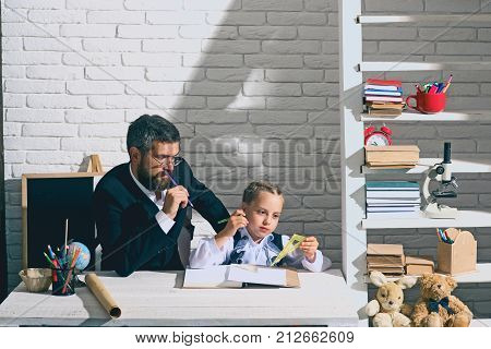 Back to school and fathers day concept. Girl and father in classroom on white brick background. Family works at desk with school items. Schoolgirl and dad with thoughtful faces hold do Maths homework