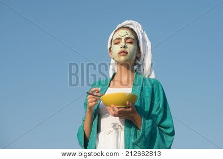 Woman With Cucumber Mask On Face On Blue Sky