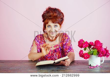 Old Woman Reading Book With Glasses At Flowers.