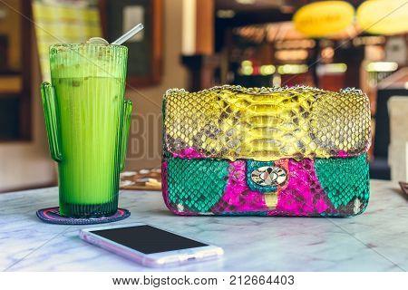 Fashion luxury snakeskin python handbag on the wooden table in restaurant.