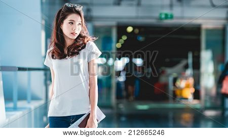 Asian women were carrying luggage around the international airport. She was traveling abroad to travel on weekends.
