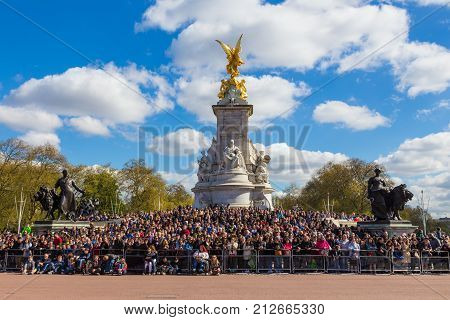 London England - 10 April 2017 - Tourists from all over the world wait arond the base of Victoria Memorial statue to see the Buckingham Palace guards marching by on April 10 2017 in London England.