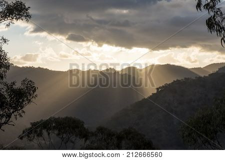 Sun rays peaking from a cloudy sky over an Australian mountain range at sunset