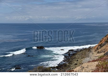 Waves breaking on a rocky coastline in southern California