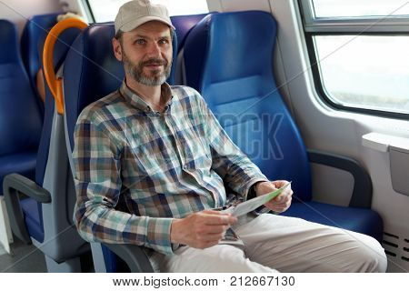Mature man holding tickets in a commuter train