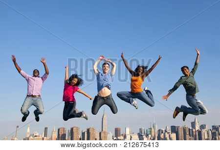 Group of multi racial people jumping in the city.