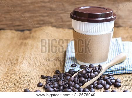 coffee plastic cup with cardboard sleeve and a pile of coffee beans placed on the wooden spoon. with copy space for text.