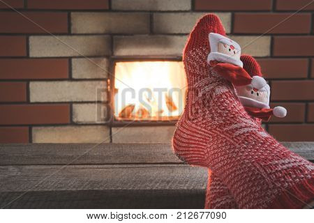Feet In Woollen Red Socks By The Fireplace. Close Up On Feet. Tabletop For Display Your Christmas Pr