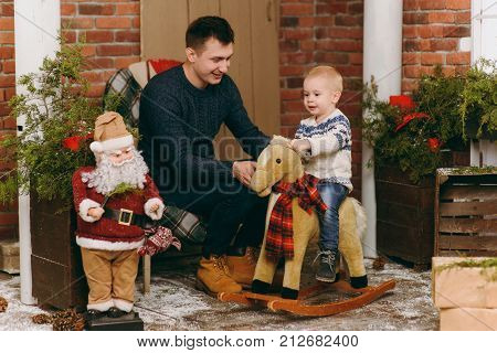 Young Happy Father With A Cute Little Child Boy On Rocking Horse, Dressed In Sweater In Decorated Ne