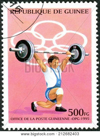GUINEA - CIRCA 1995: A stamp printed in Guinea devoted Summer Olympic Games in Atlanta shows weightlifter circa 1995
