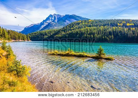 The pure turquoise water of the lake reflects coniferous forests. The Magnificent Lake Two Jack. A charming little island near the shore. The concept of ecological and active tourism