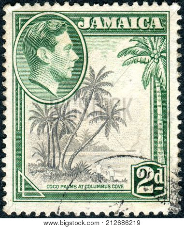 JAMAICA - CIRCA 1938: Postage stamp printed in Jamaica shows a portrait of King George VI and Coco Palms at Columbus Cove circa 1938