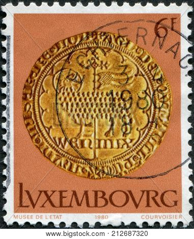 LUXEMBOURG - CIRCA 1980: A stamp printed in Luxembourg shows gold coin of the time of Wenzel von Luxemburg Easter lamb circa 1980