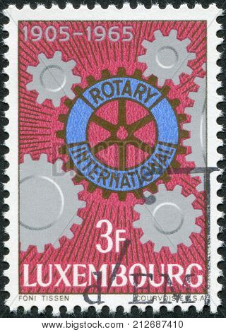 LUXEMBOURG - CIRCA 1965: A stamp printed in Luxembourg is dedicated to the 60th anniversary of Rotary International shows Rotary Emblem and Cogwheels circa 1965
