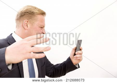 Businessman screaming while talking by phone on a white background