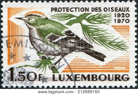 LUXEMBOURG - CIRCA 1970: A stamp printed in Luxembourg is dedicated to the 50th anniversary of the Luxembourg Society for the protection and study of birds shows Goldcrest (Regulus regulus) circa 1970