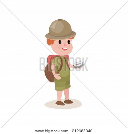 Cartoon boy scout holding compass in hand and backpack on his shoulders. Young explorer looking for way. Dressed in khaki uniform and hat. Scouting concept. Flat vector illustration isolated on white