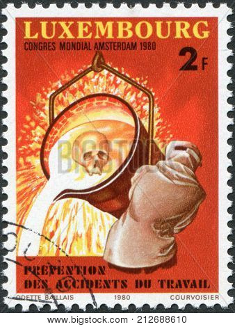 LUXEMBOURG - CIRCA 1980: A stamp printed in Luxembourg is dedicated to 9th World Congress on Prevention of Occupational Accidents & Diseases Amsterdam shows a Worker Pouring Molten Iron circa 1980